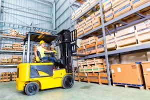 33784454 - asian fork lift truck driver lifting pallet in storage warehouse